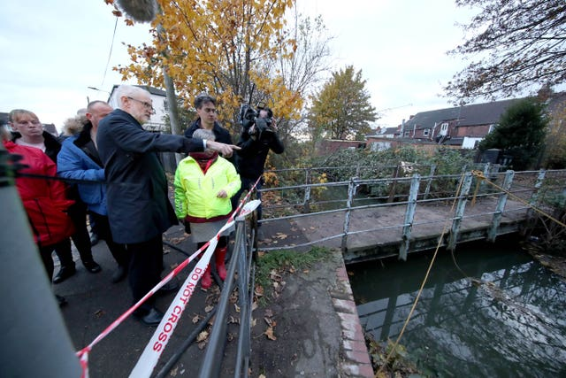 Labour leader Jeremy Corbyn (left) and former leader Ed Miliband (right) are shown the water level in Bentley, Doncaster