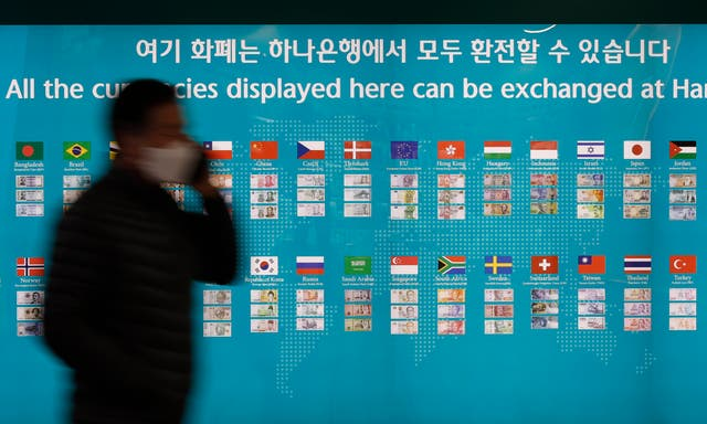 A man wearing a face mask passes a bank's currency advertisement board in Seoul