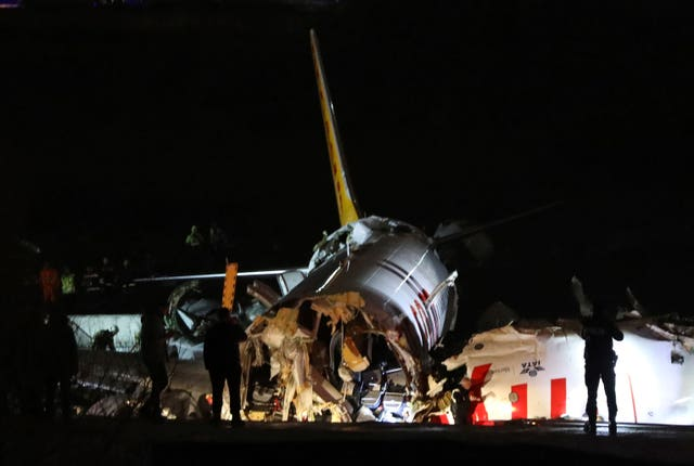 Rescue members work after a plane skidded off the runway at Istanbul's Sabiha Gokcen Airport
