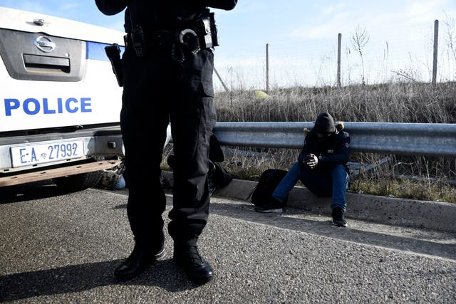 Greek police detain a migrant in the Evros region