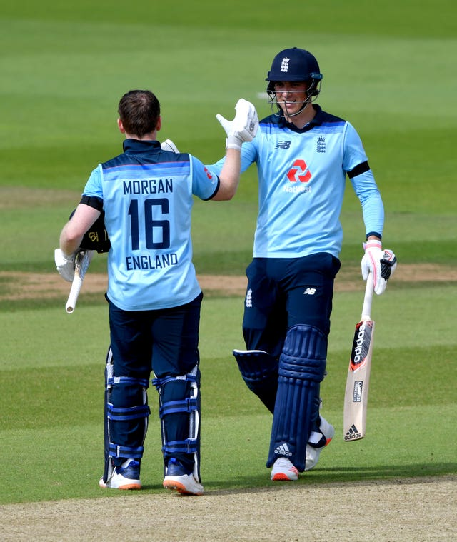 Eoin Morgan celebrates reaching his century with team-mate Tom Banton