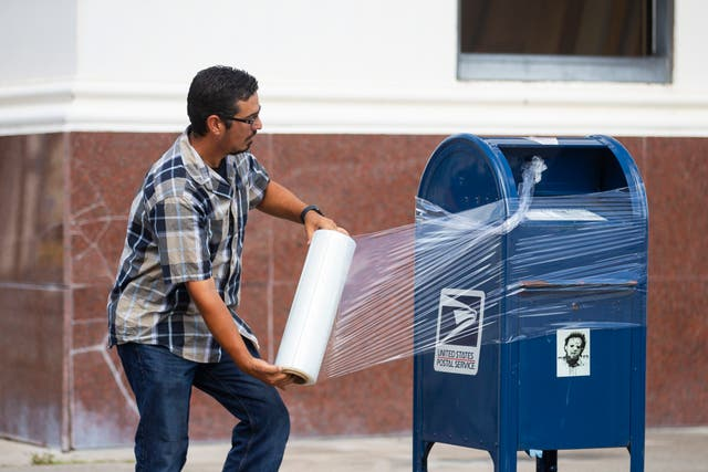A United State Postal Service employee covers a post box with plastic wrap after removing its contents in anticipation of Hurricane Laura