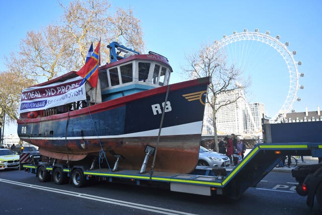 A fishing boat is towed through Westminster