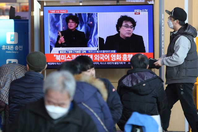 People watch a TV screen showing images of South Korean director Bong Joon Ho during a news programme at Seoul Railway Station