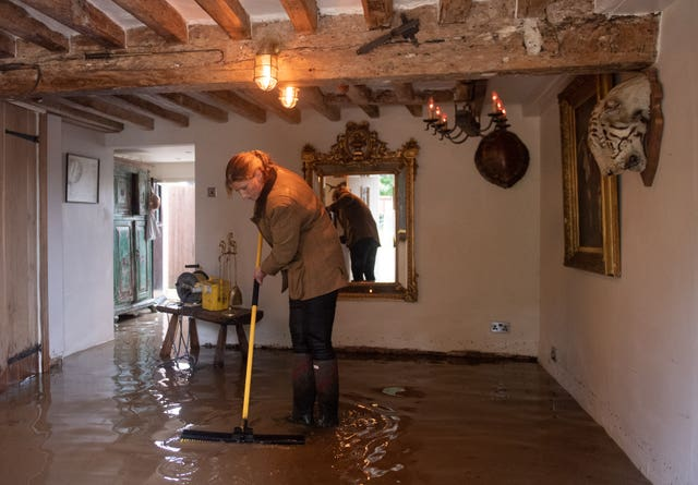 Local resident Roz attempts a clean-up operation in Cossington, as floodwaters cover the ground floor in her home