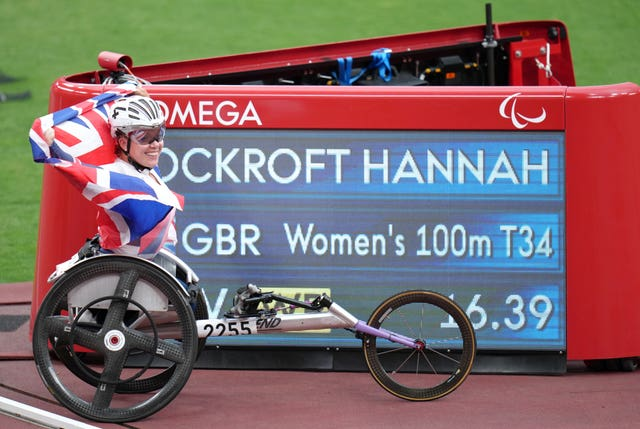 Briton Hannah Cockroft poses with the scoreboard showing her new world record