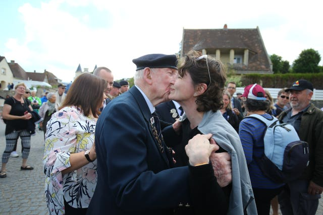 Veteran Ron Nolan is greeted by a member of the public in Arromanches