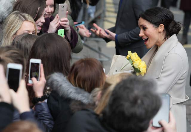 Meghan Markle being given yellow roses during a walkabout in Belfast (Brian Lawless/PA)