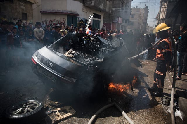 Palestinians gather around the wreckage of a vehicle following an Israeli airstrike in Gaza City