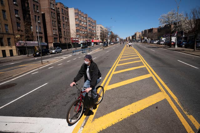 A man wearing a mask cycles along a section of the Grand Concourse that has been temporarily closed to traffic during the coronavirus pandemic in the Bronx borough of New York