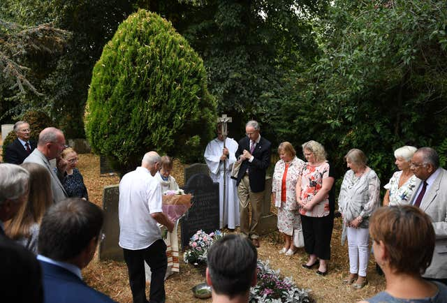 A memorial service is held around the grave of Jean Purdy