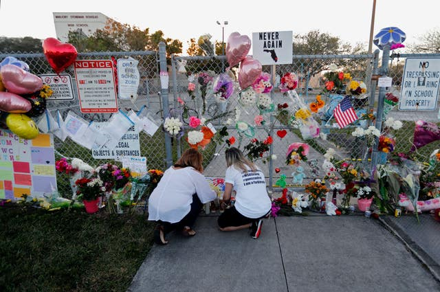 People light candles at a makeshift memorial outside Marjory Stoneman Douglas High School (AP Photo/Gerald Herbert)