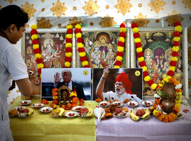 A Hindu priest performs prayers in front of portraits of US President Donald Trump and Indian Prime Minister Narendra Modi