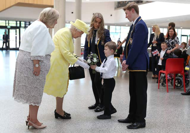 The Queen receives a posy of flowers from Archie Wilson