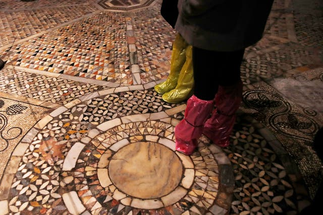 People walk on an interior mosaic floor of St Mark's Basilica in Venice, Italy