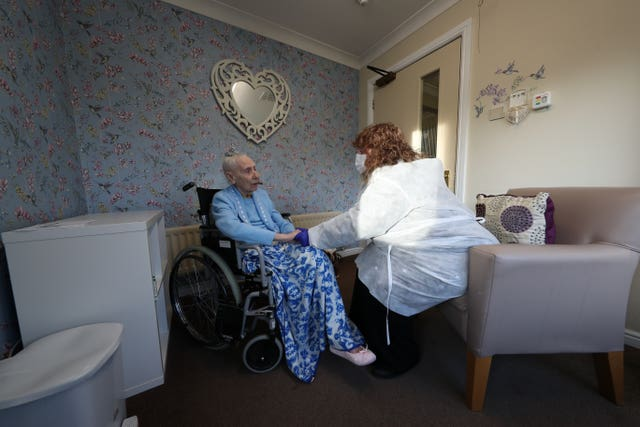Woman sat with her friend during a Christmas Day visit at a care home