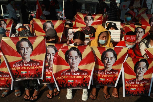 Anti-coup protesters hold identical posters with an image of deposed Myanmar leader Aung San Suu Kyi as they gather outside the Hledan Centre in Yangon, Myanmar
