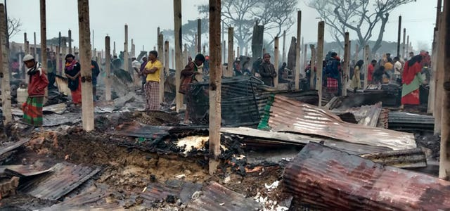 Rohingya refugees walk in the charred remains at Nayapara Camp
