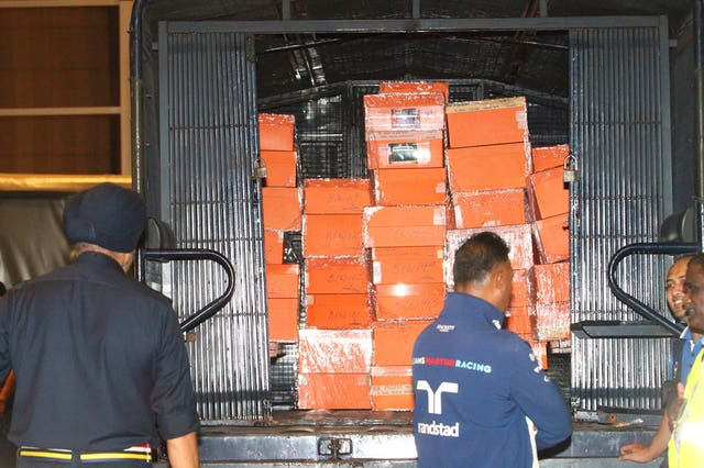 Boxes containing confiscated items are put inside a police truck in Kuala Lumpur (AP)