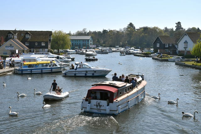 Boats cruise along the River Bure