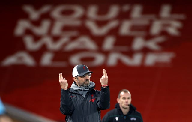Liverpool Jurgen Klopp points two fingers to the sky in front of a You'll Never Walk Alone banner on the Kop