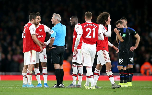 Arsenal players speak to referee Martin Atkinson, who reversed his decision to award them a third goal after consultation with the VAR