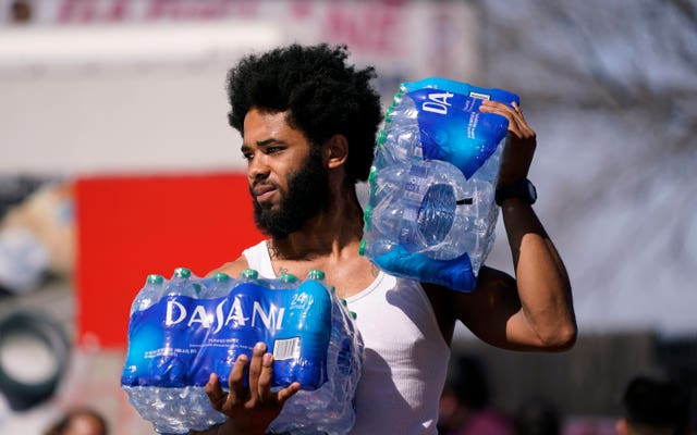 Brandon Fisher carries drinking water he was given by volunteers at an apartment complex without water in Dallas