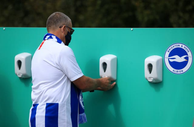 A fan attending a Brighton v Chelsea pre-season friendly using a hand sanitising station at the Amex Stadium