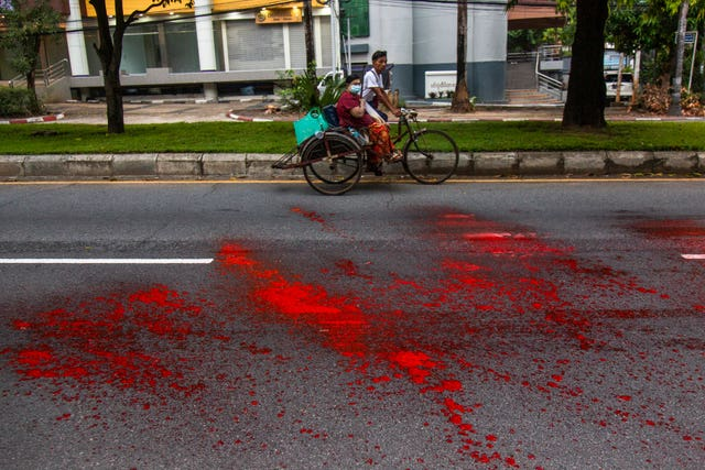 A woman riding a rickshaw passes by a street with splashes of red paint from anti-coup protesters (AP)
