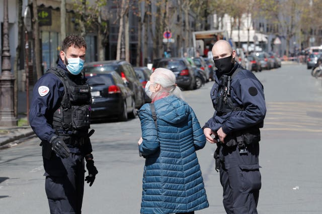 A woman talks to police officers after a shooting in Paris
