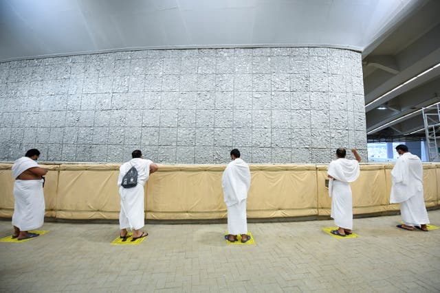 Muslim pilgrims cast stones at a pillar in the symbolic stoning of the devil