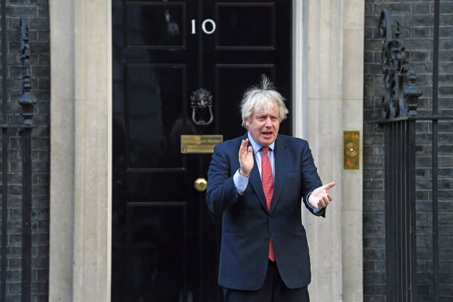 Prime Minister Boris Johnson applauds at 10 Downing Street