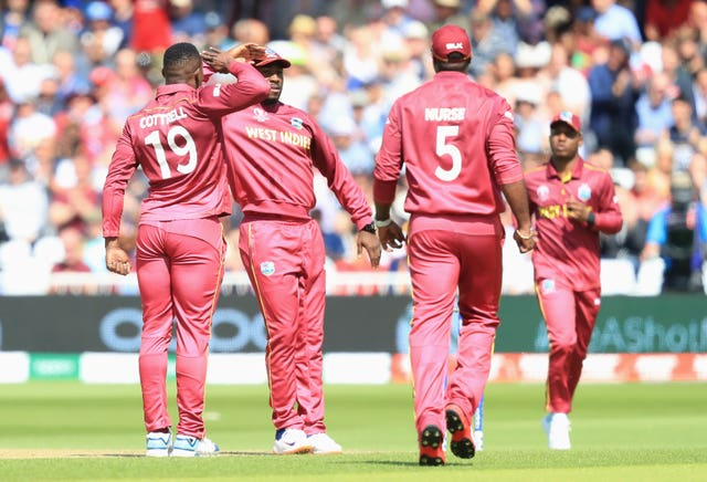 Sheldon Cottrell, left, follows a wicket with his trademark celebration
