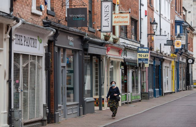 A woman wearing a face mask walks along a street of closed shops in Leicester (Joe Giddens/PA)