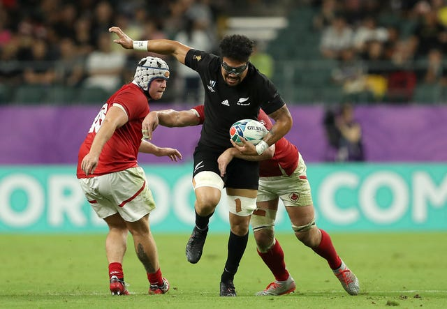 Ardie Savea breaks a tackle from Canada's Lucas Rumball, right