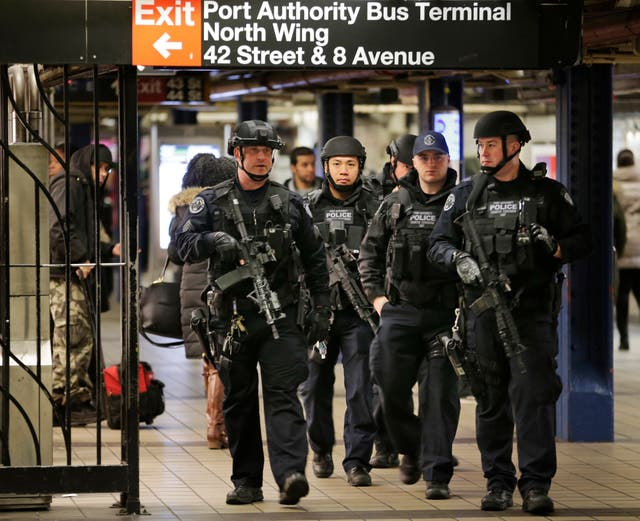 Police officers in December 2017 patrol in the passageway connecting New York City's Port Authority bus terminal and the Times Square subway station, near the site of an explosion the previous day