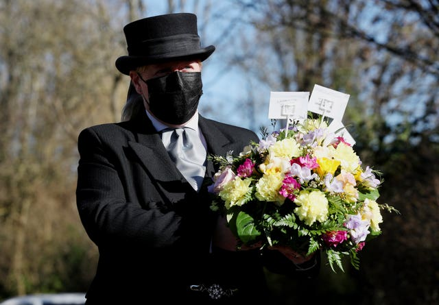 Funeral director Colette Sworn gathers a floral tribute as part of her preparations to oversee a funeral at Co-op Funeralcare in Watford, Hertfordshire