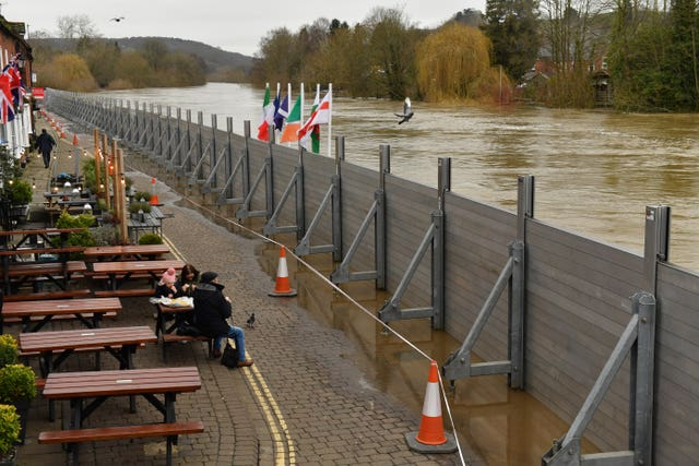 People eating in front of temporary flood defences in Bewdley, Worcestershire