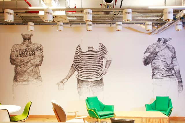 (Black and white torsos on the wall inside Facebook's new London office loom over green chairs (Ben Lister/PA)