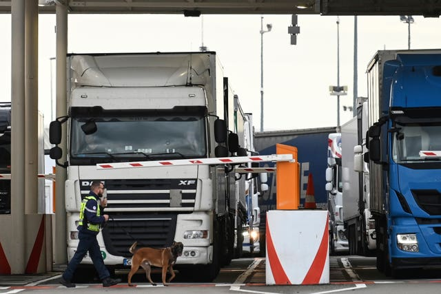 An employee of Eurotunnel and his dog check a truck on its way to Britain