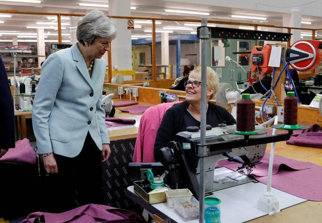 Prime Minister Theresa May speaks to a worker during a visit to Boss Design (Darren Staples/PA)
