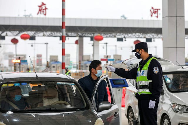 A policeman uses a digital thermometer to take a driver's temperature at a checkpoint at a highway toll gate in Wuhan in central China's Hubei Province