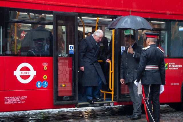 The Prince of Wales steps off an electric bus as he and the Duchess of Cornwall arrive for a tour of the London Transport Museum
