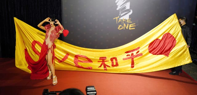Chinese-American actress Bai Ling poses with her slogan 'Love, Peace' at the 57th Golden Horse Awards in Taipei, Taiwan