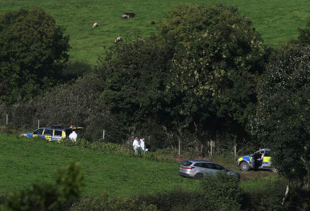 Police and forensics officers at farmland in Killen, around a mile from Castlederg (Brian Lawless/PA)
