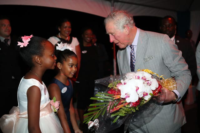 The Prince of Wales is presented with flowers as he attends the Governor-General's Reception at the Serenity Hotel, Coconut Bay, St Lucia