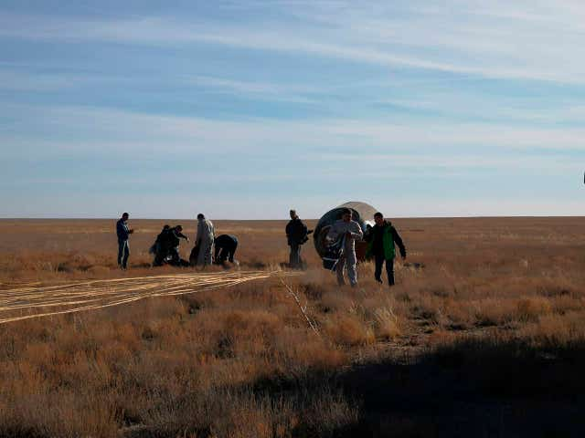The Soyuz MS-10 space capsule lays in a field after an emergency landing