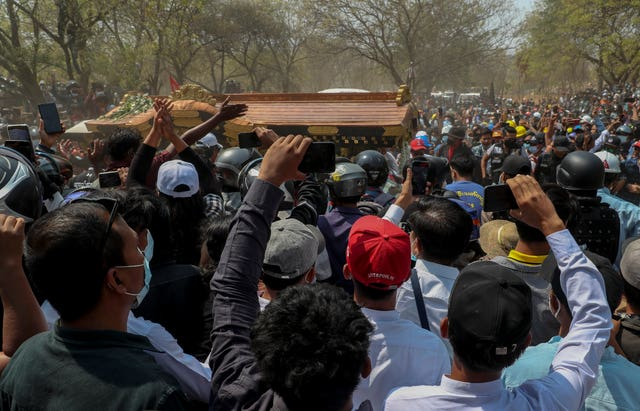 The body of a protester arrives at a cemetery in Mandalay