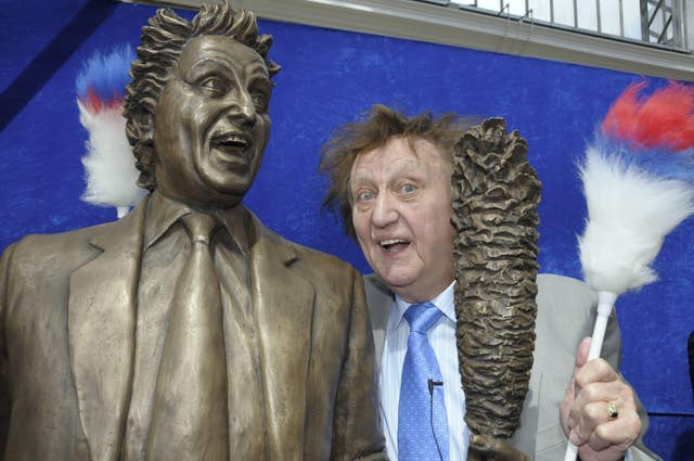Ken Dodd poses with a bronze statue of himself