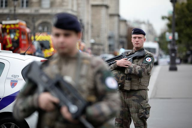 Armed soldiers patrol after the incident in Paris